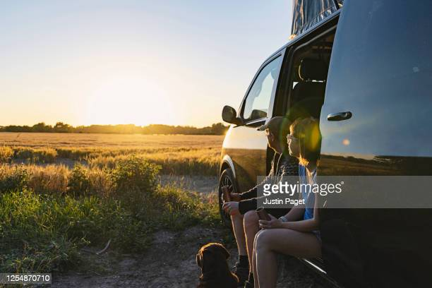 couple with their pet dog at sunset - camper van stock pictures, royalty-free photos & images