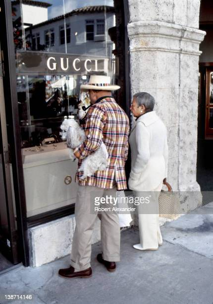 A couple with their poodle window shop along exclusive Worth Avenue in Palm Beach Florida