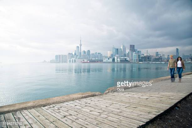couple with toronto skyline - toronto stock pictures, royalty-free photos & images