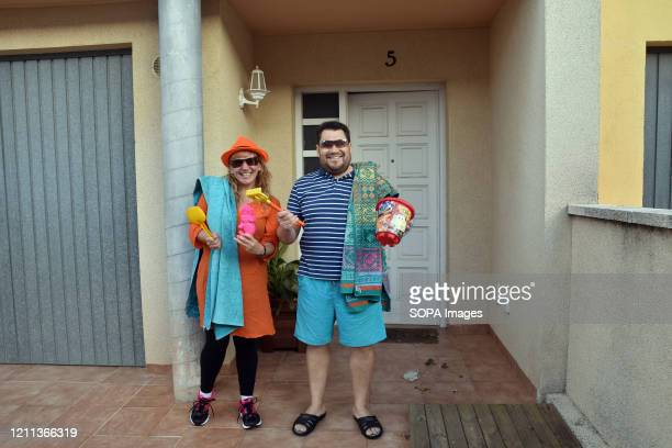 A couple with towels hold children's beach accessories on the terrace of their house during the confinement amid Coronavirus crisis Residents of Mas...