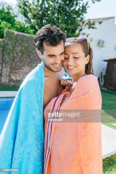 couple with towels hugging at the poolside - wrapped in a towel stock pictures, royalty-free photos & images