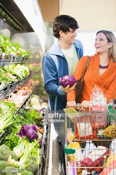 Couple with trolley buying vegetables in supermarket