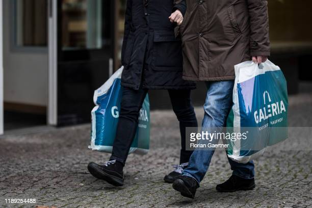 Couple with two bags of Galeria Kaufhof are pictured on December 17, 2019 in Berlin, Germany.