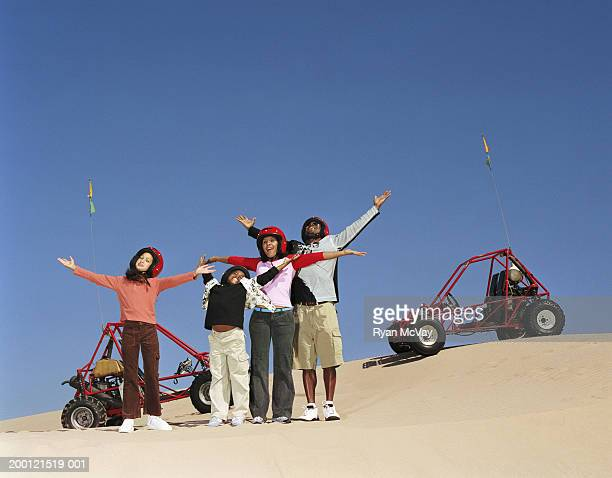 Couple with two children (8-10) standing in sand beside dune buggies
