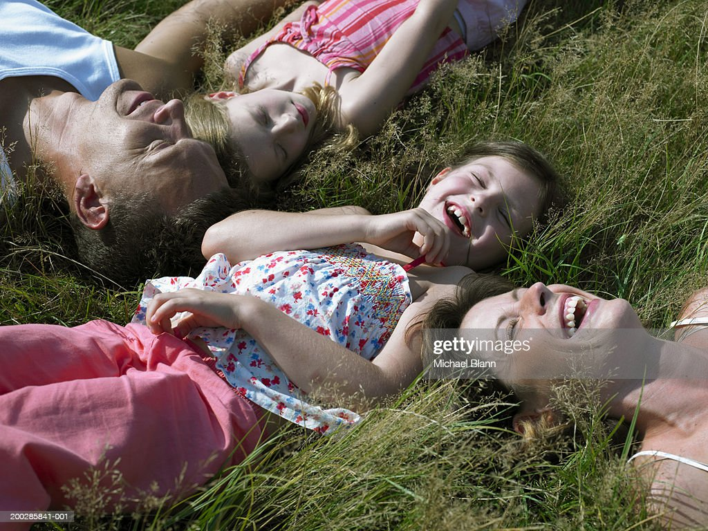 Couple with two daughters (6-9) lying on grass laughing : Stock Photo