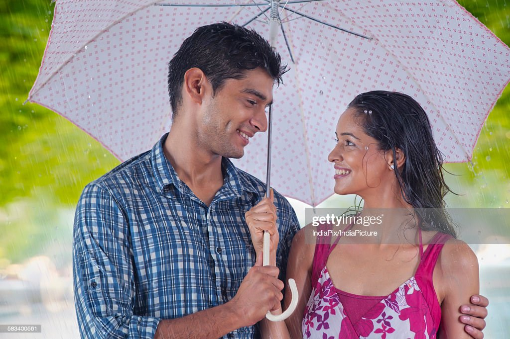 Couple with umbrella enjoying the rain : Stock Photo