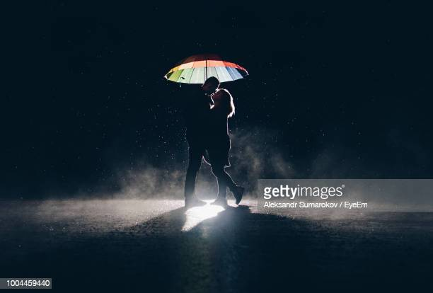 couple with umbrella standing against sky at night - moonlight lovers stock-fotos und bilder