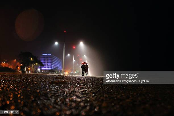 Couple With Umbrella Walking On Street Against Sky At Night During Monsoon