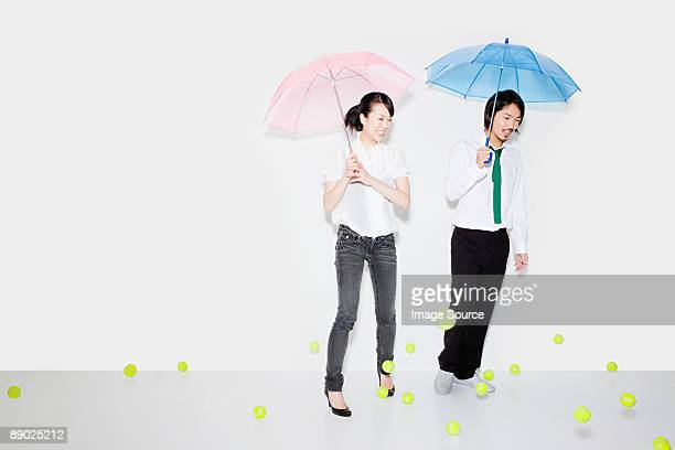 Couple with umbrellas and falling tennis balls