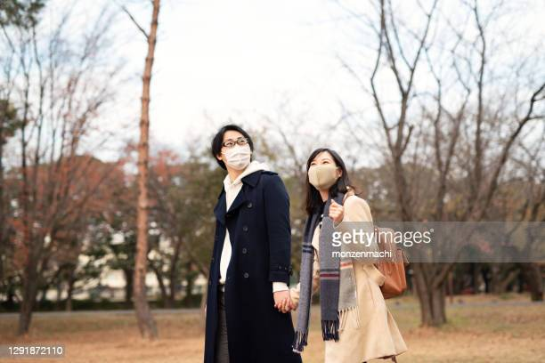 couple with wearing mask dating in autumn park - saitama prefecture stock pictures, royalty-free photos & images