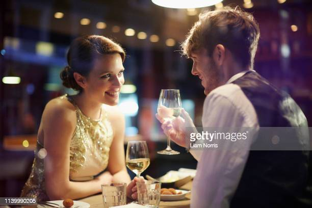 couple with wine glasses in restaurant - romance stock pictures, royalty-free photos & images