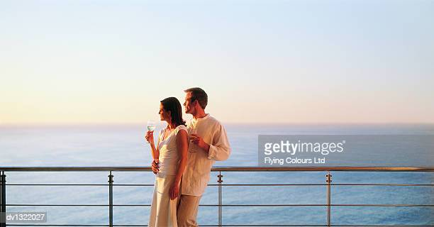 couple with wine glasses standing by railing and looking at view. - veiligheidshek stockfoto's en -beelden