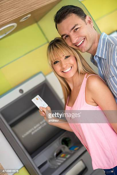 Couple de retirer de l'argent à un distributeur automatique de billets