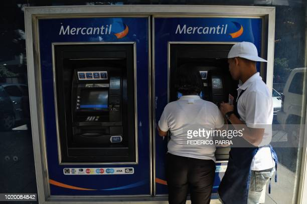 Couple withdraws money from an ATM in Caracas on August 20, 2018. - Caracas is issuing new banknotes after lopping five zeroes off the crippled...