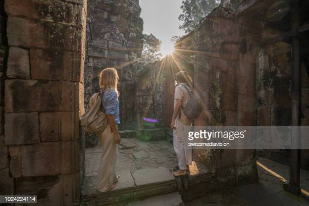 couple wonderlust concept traveling and discovering ancient temples at sunset, asia. two people travel explore vacations togetherness concept - angkor wat stock pictures, royalty-free photos & images