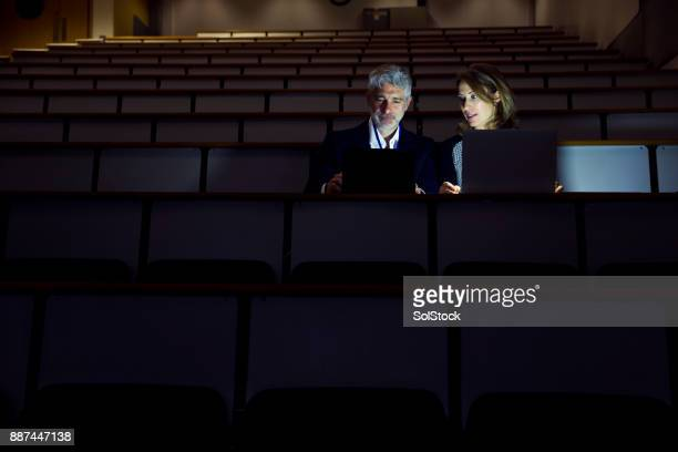 Couple Working Alone in a Seminar Room in the Dark
