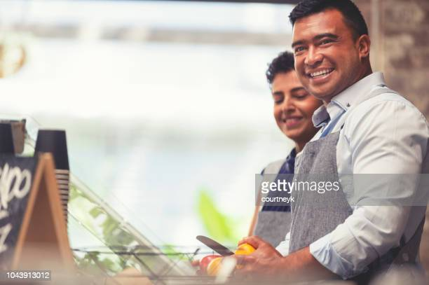 couple working at a small retail food restaurant. - happy merchant stock pictures, royalty-free photos & images