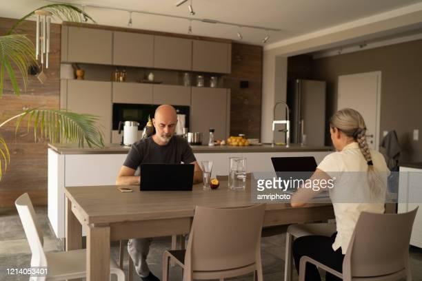 casal trabalhando de casa durante a quarentena covid-19 - lockdown - fotografias e filmes do acervo