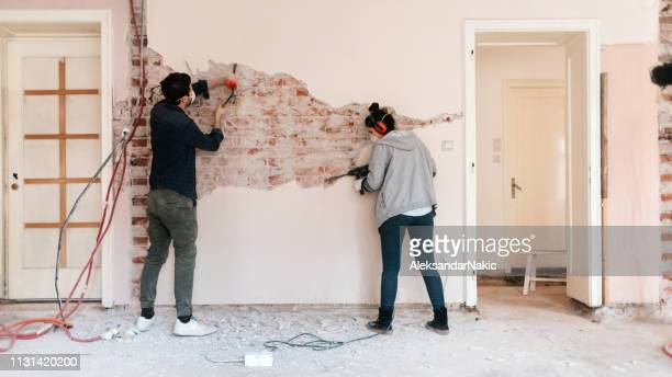 couple working on reconstruction of their apartment - home improvement stock pictures, royalty-free photos & images