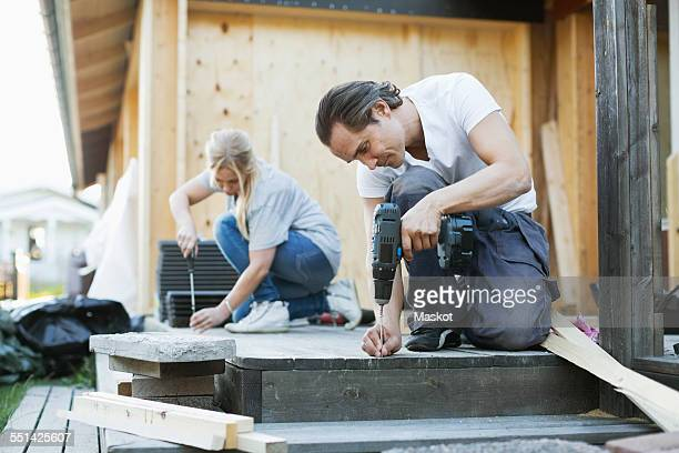 couple working outside house during home improvement - renovierung themengebiet stock-fotos und bilder