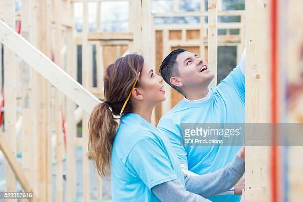 Coppia lavorando insieme per costruire casa per beneficenza