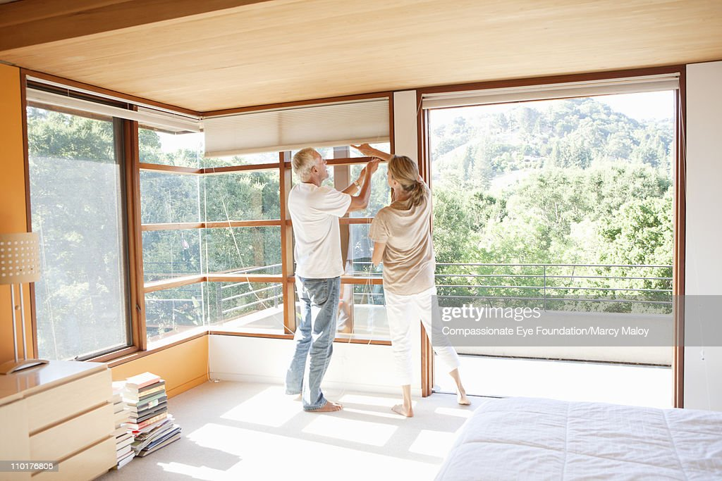 Couple working together to use window blinds : Stock Photo