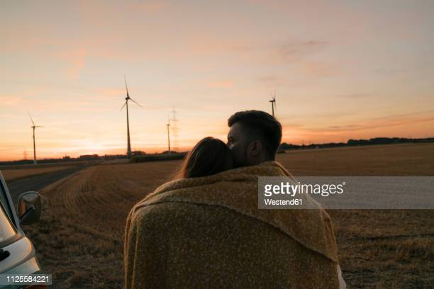 couple wrapped in a blanket at camper van in rural landscape with wind turbines in background - hot couple photos et images de collection