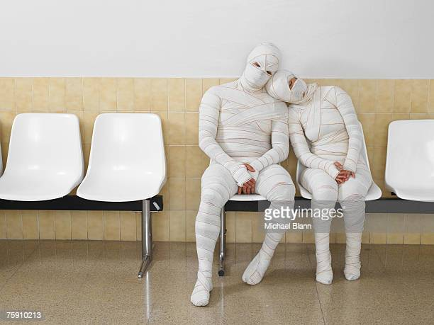 couple wrapped in bandages leaning together - outpatient care stock pictures, royalty-free photos & images