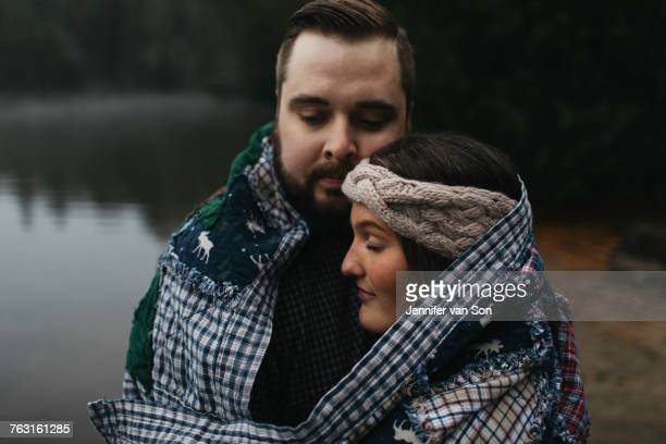 Couple wrapped in blanket eyes closed hugging