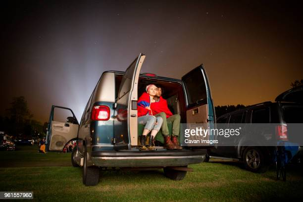 couple wrapped in blanket sitting at back of car during drive-in movie - autokino stock-fotos und bilder