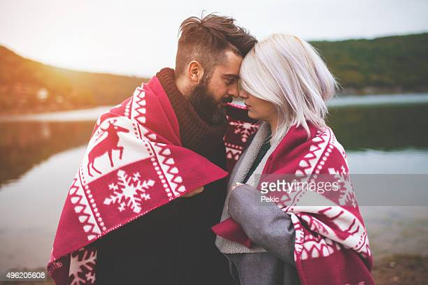 Couple wrapped in blanket standing by the lake