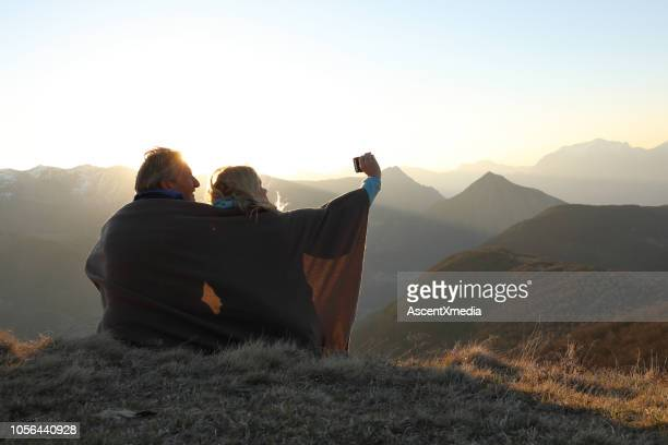 couple wrapped in blanket take photo - mature couple stock pictures, royalty-free photos & images