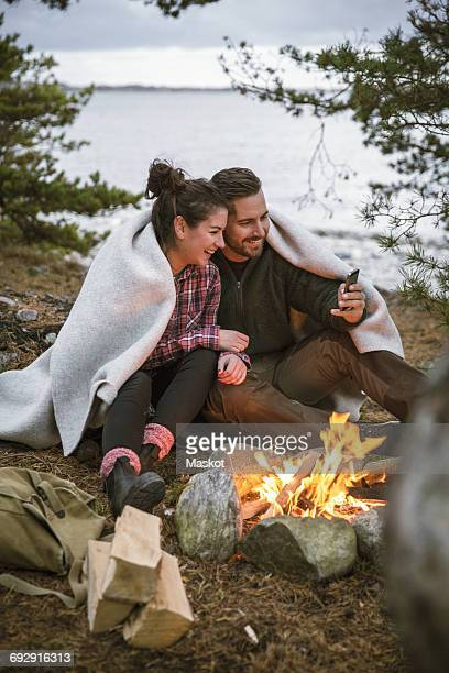 Couple wrapped in blanket using mobile phone while sitting by fire pit at campsite