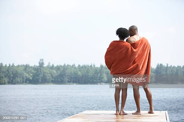 Couple wrapped in towel, standing on pier, rear view