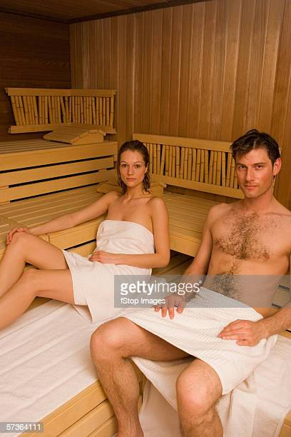 couple wrapped in towels and sitting in sauna - female hairy chest stock pictures, royalty-free photos & images