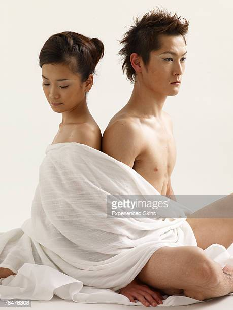 A couple wrapped in white cloth, sitting