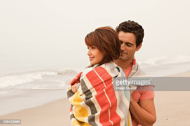 Couple enveloppé dans une couverture colorées sur la plage