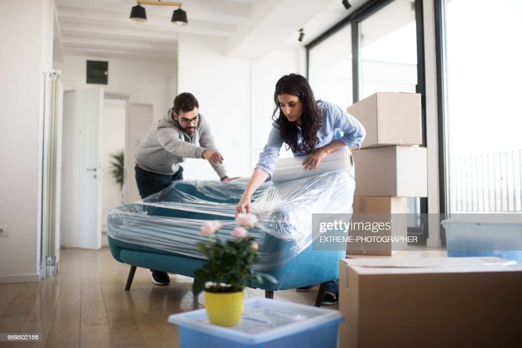 Couple wrapping up sofa : Stock Photo