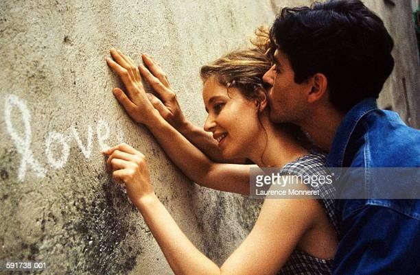 couple writing 'love' in chalk on wall, close-up - linkshandig stockfoto's en -beelden