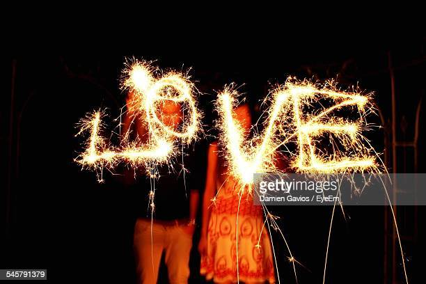 Couple Writing Love With Sparklers At Night