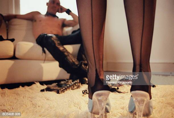 Couple,man sitting on sofa,fetish toys on floor,woman's legs in fore