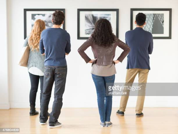 couples admiring art in gallery - art gallery stock pictures, royalty-free photos & images