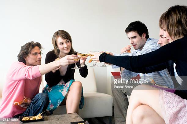 2 couples and a man clinking glasses of champagne