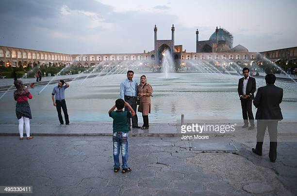 Couples and families spend in the Unesco-listed Naqsh-eJanan Square on June 2, 2014 in Isfahan, Iran. Isfahan, with it's immense mosques, picturesque...