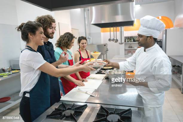 Couples at a cooking class learning how to make a dessert looking very happy