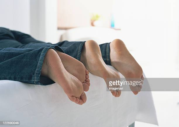 couple's barefoot - woman lying on stomach with feet up stock photos and pictures