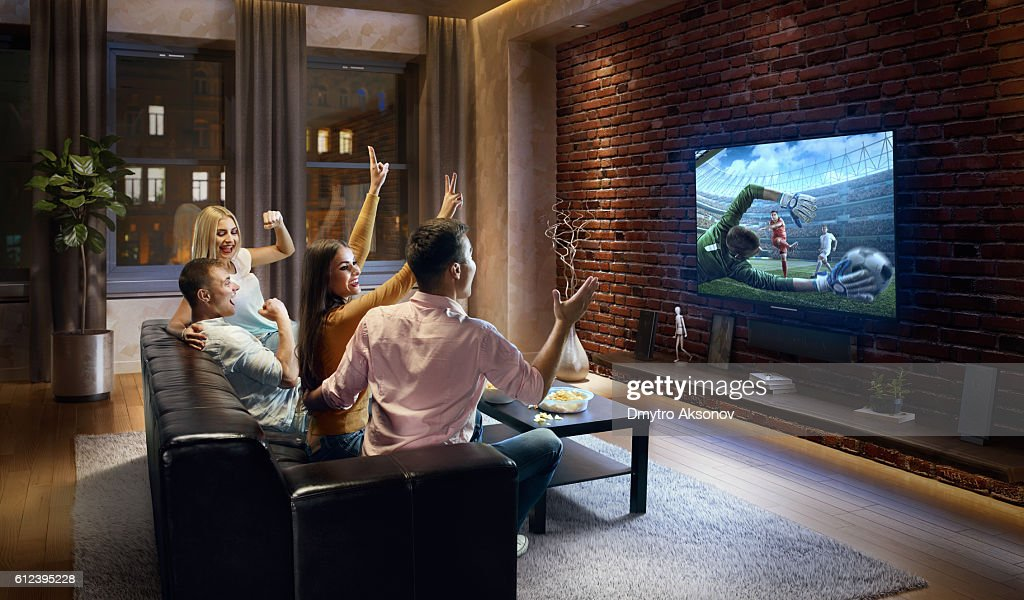 Couples cheering and watching soccer game on TV : Stock Photo