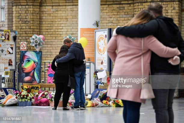 Couples console each other at the floral memorial in place at Victoria station during the commemoration People gather at Victoria station to mark the...