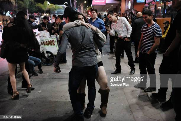 Couples dance along Revolution Avenue at night on January 20 2019 in Tijuana Mexico Despite one of the most violent years on record for the border...