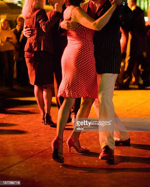Couples dancing Argentine Tango outdoors at night, focus on legs.